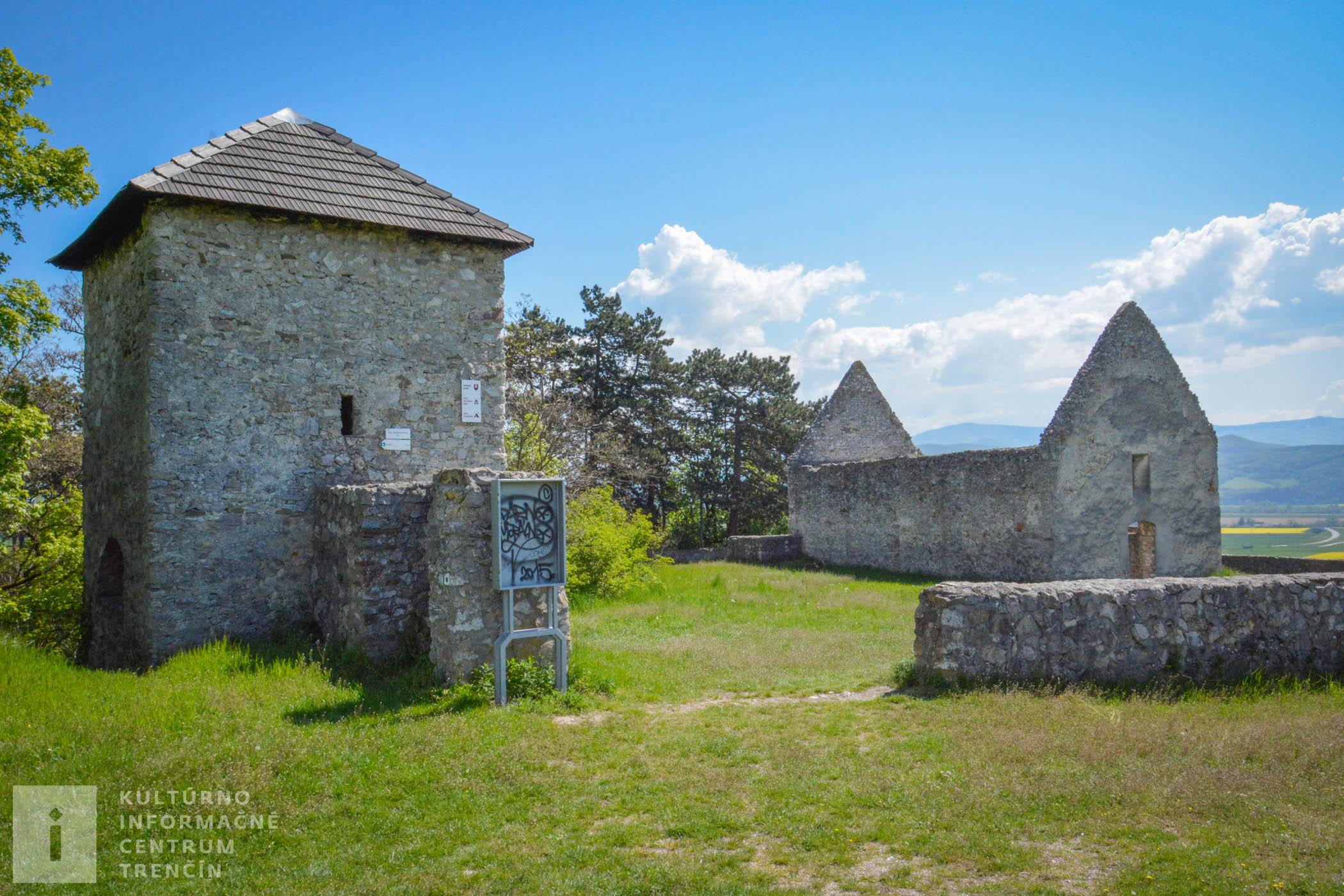 Vľavo sa nachádza z časti obnovená strážna veža a vpravo pozostatky románskeho kostolíka v Haluziciach