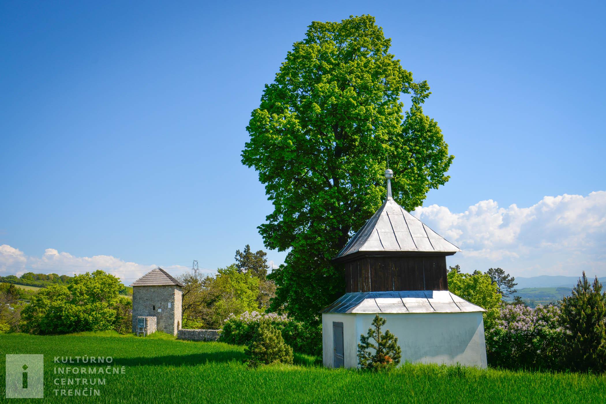 Vdiaľke vidno strážnu vežu pri kostolíku Všetkých svätých v Haluziciach. V popredí sa nachádza